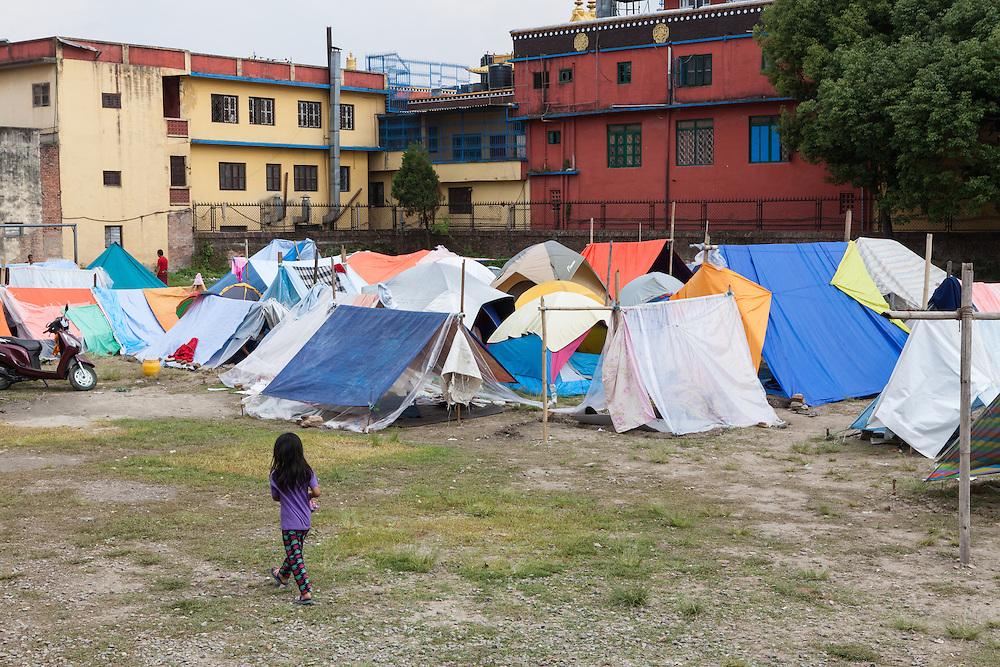 Meisje loopt door een tentenkamp in de wijk Boudhanath. Klooster op de achtergrond.