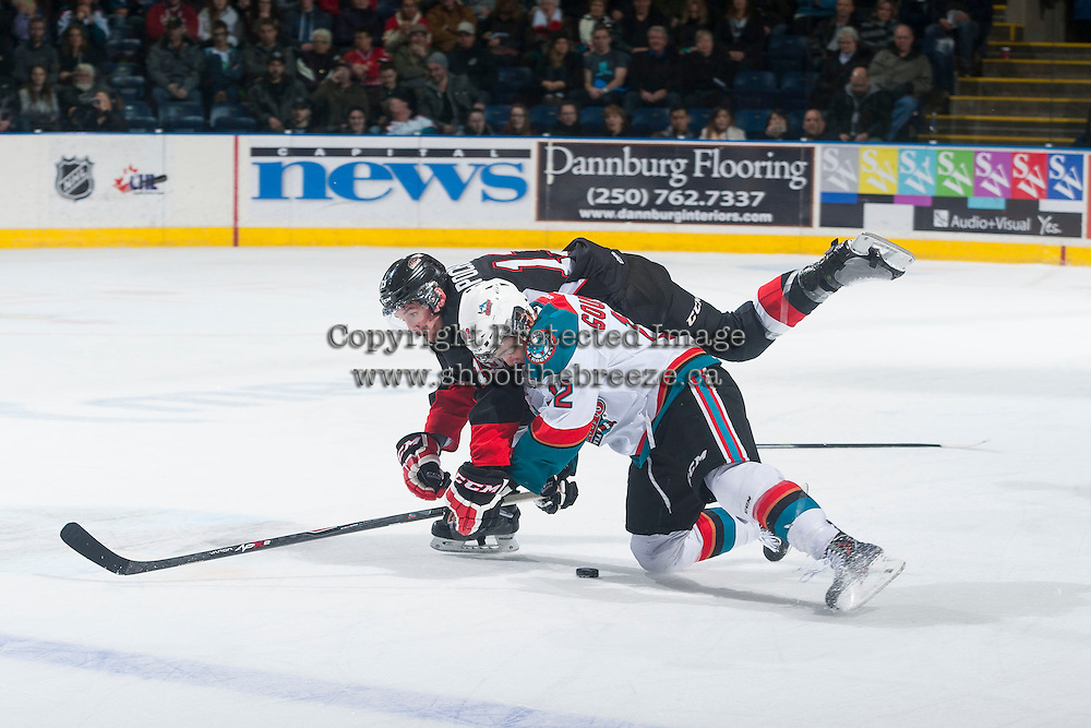 KELOWNA, CANADA - DECEMBER 30: Zach Pochiro #13 of Prince George Cougars is checked to the ice by Tyrell Goulbourne #12 of Kelowna Rockets during the second period on December 30, 2014 at Prospera Place in Kelowna, British Columbia, Canada.  (Photo by Marissa Baecker/Shoot the Breeze)  *** Local Caption *** Tyrell Goulbourne; Zach Pochiro;