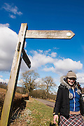 Annandale Way, Lochmaben, young woman wearing black jacket, blue jumper, greay wooly hat and tartan skirt walks smiling past Annandale Way walk signpost infront of fields and trees on a sunny day with blue sky and cloud cover.