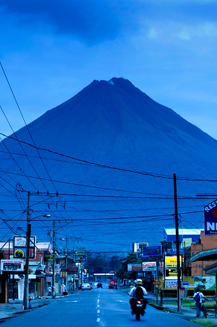 The very active Arenal Volcano looms over the tourist town of La Fortuna, Costa Rica at dusk.