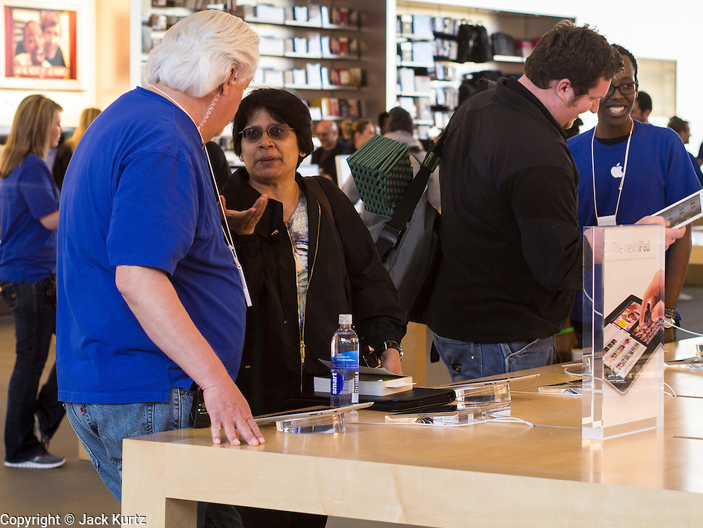 16 MARCH 2012 - SCOTTSDALE, AZ:  Apple Store employees help consumers looking at the New iPad at the Apple Store in Scottsdale, AZ, Friday. Several hundred people were in line at the Apple Store in the Scottsdale Quarter in Scottsdale, AZ, Friday to buy the New iPad.   PHOTO BY JACK KURTZ