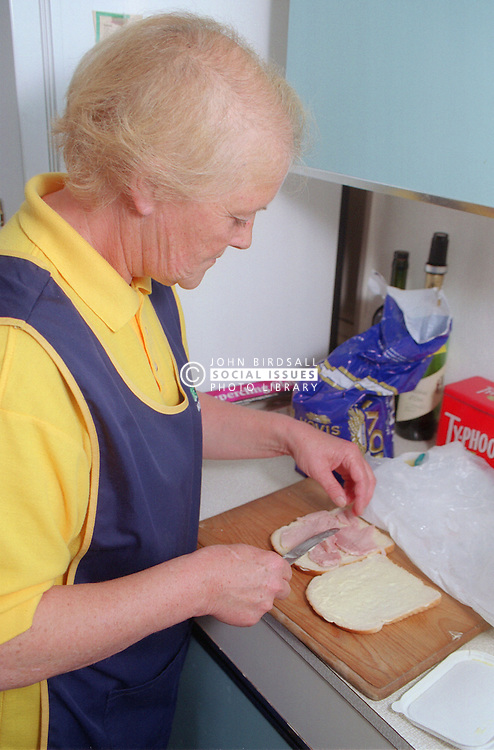 Elderly carer preparing sandwich for client,