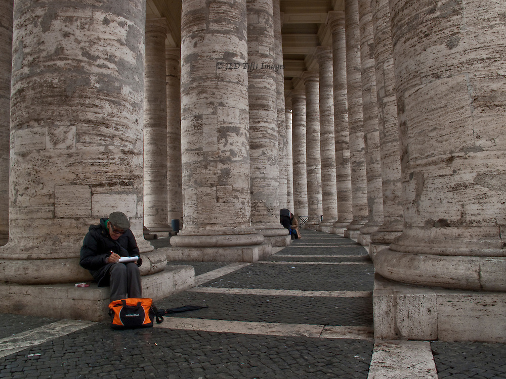 St Peter's Square, Bernini colonnade, interior curve; man seated writing in the foreground, orange backpack at his feet; another figure partly visible behind another column.