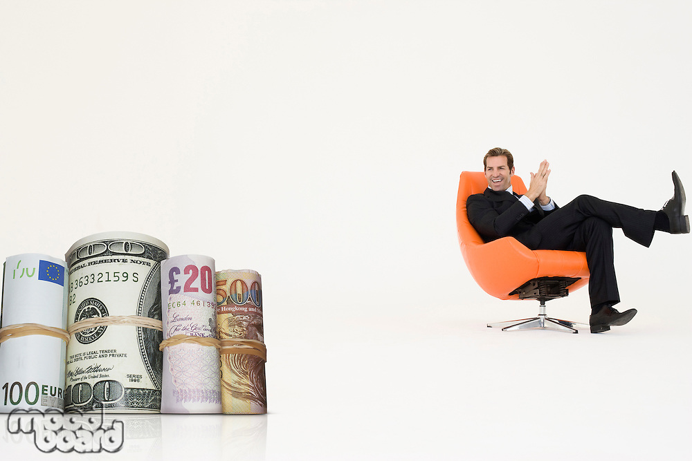 Happy businessman looking at money rolls representing growth in international business