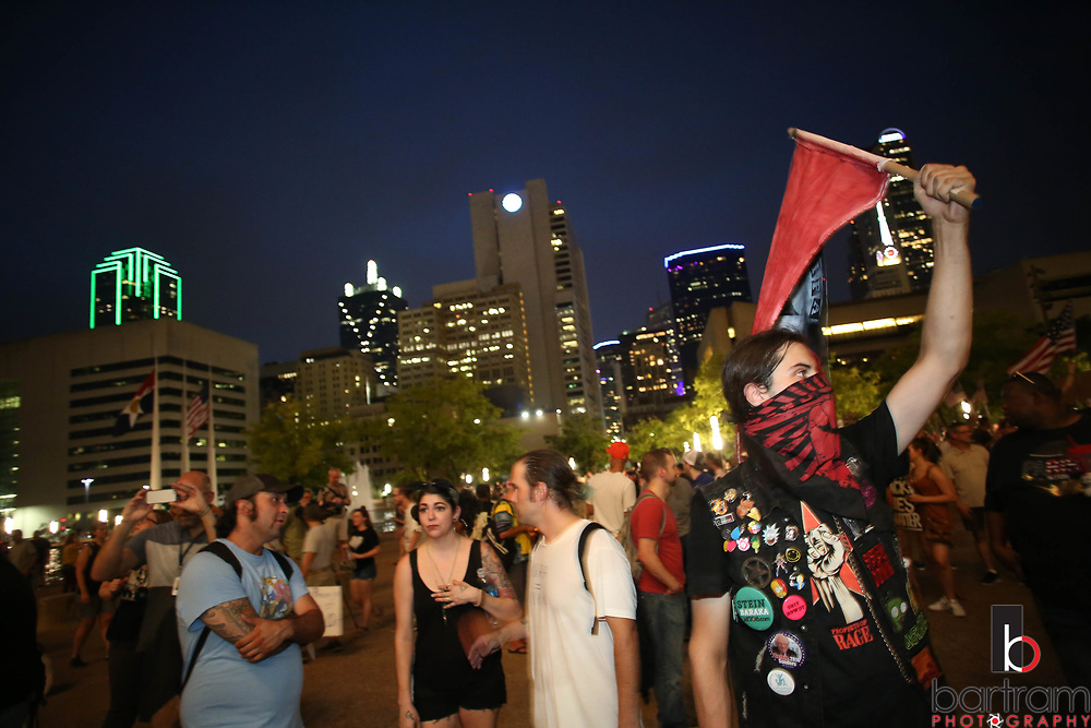 Jonesy Jones of Dallas waves a flag during an anti white-supremacy rally at Dallas City Hall plaza on Saturday, Aug. 19, 2017. (Photo by Kevin Bartram)