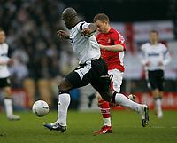 Derby centre half Darren Moore (white) prepares to tackle Wrexham's Matty Done (red)