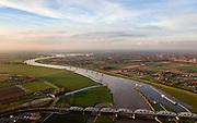 Nederland, Noord-Brabant, gemeente Grave, 15-11-2010. Maaskant, .stuw en sluis bij Grave. Maas gezien naar het noordoosten. Het sluis- en stuwcomplex is gebouwd in het kader van de Maasnormalisatie. De Maas is een regenrivier, met met name in de winter grote wateraanvoer (ook door smeltwater). De vakwerkbrug is voor lokaal verkeer..Weir and lock at Grave. The lock and weir (or dam) complex is built during the Meuse Standardization. The river Meuse is a rain river, with high water levels, especially during the winter (also by melt water). The truss bridge for local traffic..luchtfoto (toeslag), aerial photo (additional fee required).foto/photo Siebe Swart