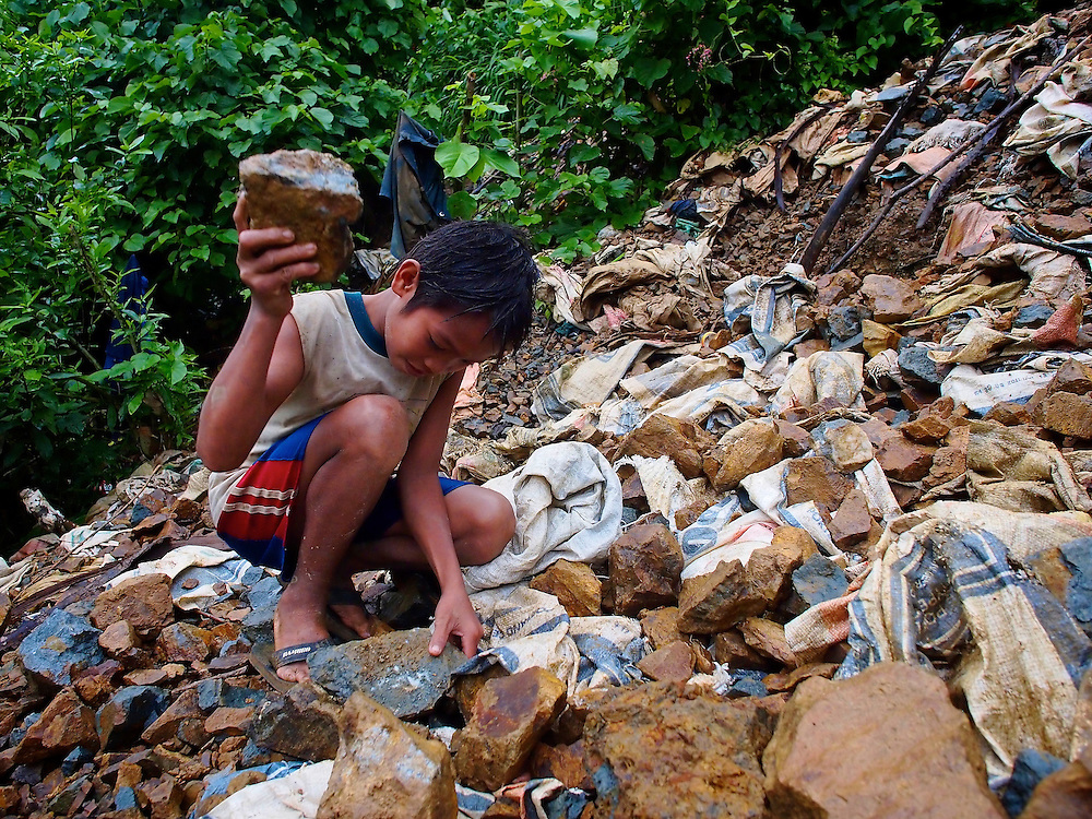 Young men and teenagers use hammers to break larger chunks of gold ore by hand.  The ore is then bagged for later processing into pure gold.  Here, a young boy inspects freshly-mined chunks of gold ore before the breaking process...Story Summary:.Small-scale gold mining in the Philippines uses mercury and cyanide to extract elemental gold from ore extracted from mines and pits dug by hand.  Very young children, some as young as four, are put to work at less dangerous but still rigorous tasks in the gold mining areas.  These include panning in streams or rivers and hauling ore sacks that can weigh up to 60 pounds.  Children often play near mechanized equipment and highly toxic mercury and cyanide.  These chemicals, used to help extract elemental gold from ore, are leached into nearby watersheds where fish and other marine life, mainstays of the Philippine diet, are poisoned.  The high price of gold and the poor economy in many developing countries has led to an increase in small-scale gold mining throughout the world.
