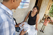 Health worker Rigoberto Martinez hands medicine to treat Leichmaniasis to local health volunteer Nosmara Mendez at her home in Coyolito, Honduras on Thursday April 25, 2013. The medicine is intended for a patient who lives in the area.