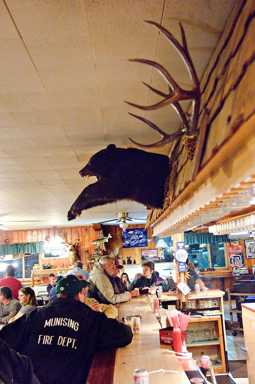 Bar scene from the Bear Trap Inn in Van Meer Michigan showing whitetail deer antlers and black bear shoulder mount.