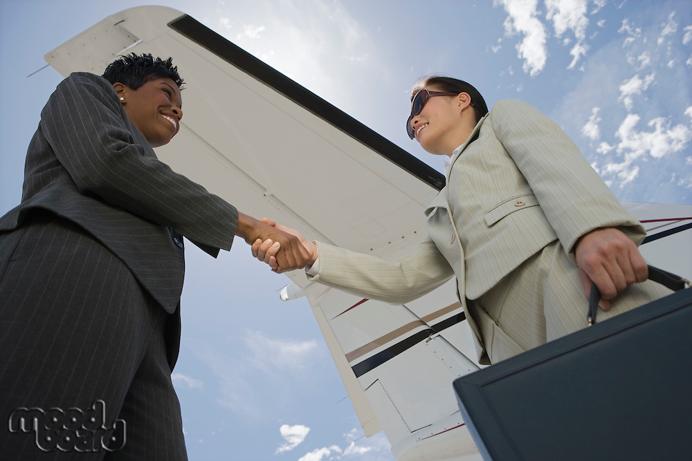 Two mid-adult businesswomen shaking handsin front of private plane, low angle view.