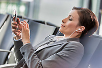 Portrait of businesswoman listening to music on smartphone while waiting for boarding in airport