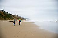 Couple walking down beach on Oregon Coast