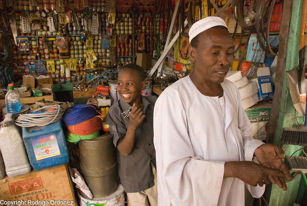"Trader Mohammed Abdulrahman, from El Muglad (right), owns a hardware store in the market of Abyei. Recent developments in Abyei town are making people settle down. ""No one was thinking of using these materials before."""