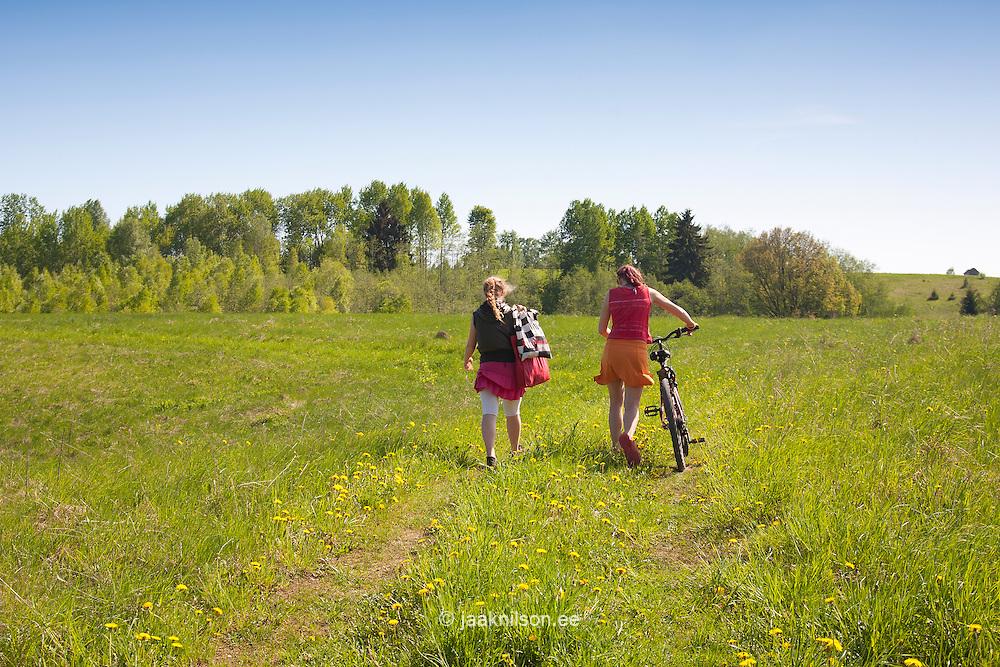 Two Girls Walking Away in Meadow, Estonia. Bicycle, Spring, Rural Landscape.