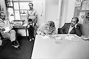 Nederland, Nijmegen, 17-2-1986<br /> Serie beelden gemaakt voor twaalf verhalen in het blad Intermediair eind 1985, begin 1986 over de staat van de nederlandse economie per provincie . De gastarbeidwinkel in de Nijmeegse wijk Bottendaal. Hier verleenden vrijwilligers hulp aan gastarbeiders, allochtonen, uit vooral Turkije en Marokko. Hier helpt een vrouw met het invullen van formulieren.<br /> De computer deed voorzichtig zijn intrede, er bestond geen mobiele telefoon, gsm, of internet . De analoge maatschappij . Transitie naar het computertijdperk en automatisering, robotisering . <br /> Foto: Flip Franssen