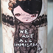 But Not Illegal ! written on fave of &quot;We are all immigrants, Anime Girl &quot;urban graffiti  sticker art  on side of street poll base  in Manhattan.<br /> <br /> Sticker art (also known as sticker bombing, sticker slapping, slap tagging, and sticker tagging) is a form of street art in which an image or message is publicly displayed using stickers. <br /> <br /> These stickers may promote a political agenda, comment on a policy or issue, or comprise a subcategory of graffiti.