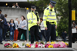 © Licensed to London News Pictures. 05/06/2017. London, UK. City workers and residents leave flowers for the victims after a terror attack that killed 7 people on London Bridge and at Borough Market in central London. Photo credit: Tolga Akmen/LNP