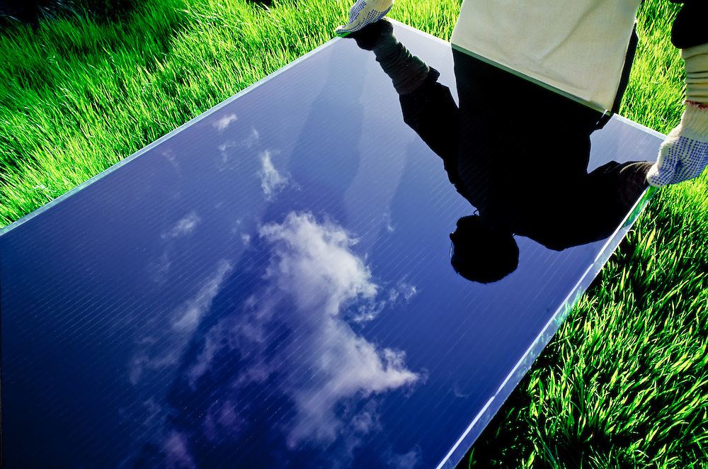 Solar Panel held by worker in green field