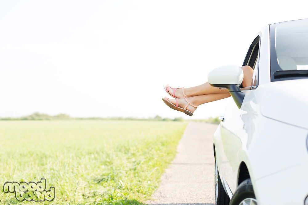 Low section of woman relaxing in car on country road