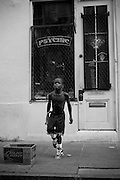 Young boy tap dancing with homemade tap shoes on Bourbon Street in the French Quarter of New Orleans.