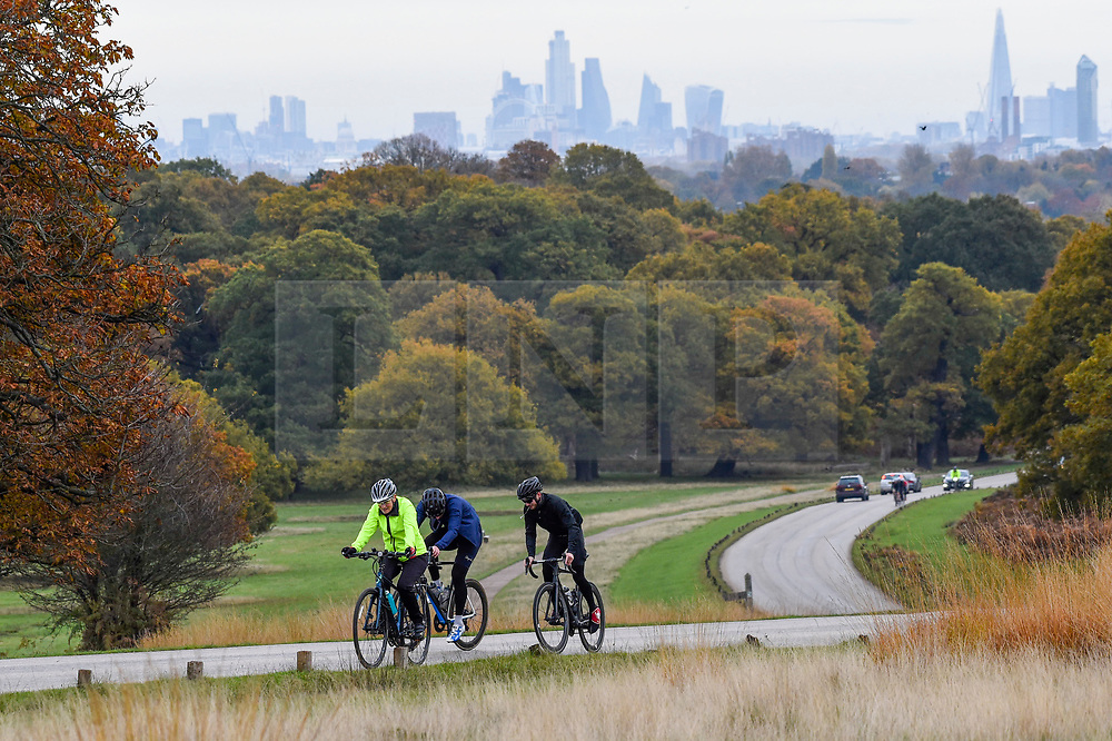 © Licensed to London News Pictures. 09/11/2019. LONDON, UK.  The tall buildings of the capital are seen behind trees showing their autumn colours as cars and cyclists pass by in Richmond Park.  Photo credit: Stephen Chung/LNP