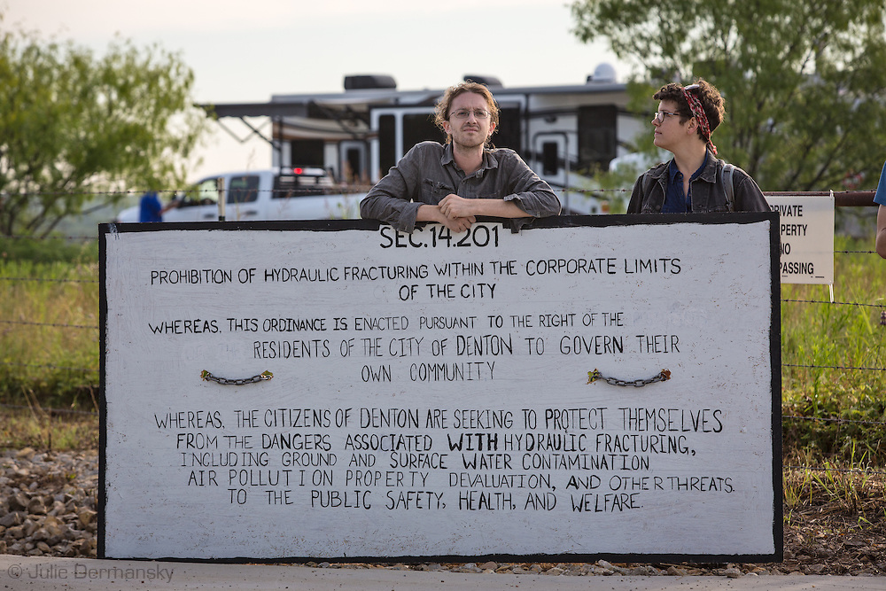 June 1, 2015, Activists hold a sign that spells out the fracking ban that citizens of Denton voted for.  Three members of the Denton Drilling Awareness Group were arrested when they refused to move away from the entrance to a fracking site where work began on June 1 despite a fracking ban the citizens of Denton voted for seven months ago.  Texas Governor Greg Abbott signed legislation, HB 40, that prohibits cities and towns in Texas from banning fracking