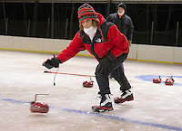 Richard Hawes watches as Sandra Ware throws a stone for the red team during the weekly curling tournament at the Gilford Ice Rink through Gilford Parks and Rec on Thursday evenings.  (Karen Bobotas/for the Laconia Daily Sun)