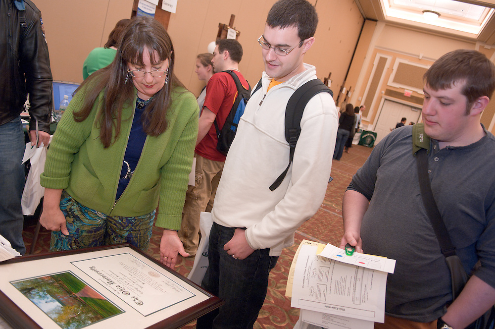 "Victoria McFadden, from Alumni Relations shows diploma frames to Evan Koontz and Jason Denhart..Ohio University Graduation Fair 2008: Countdown to Commencement was on April 16 in Baker University Center Ballroom. The event offered ""one-stop shopping"" for all things graduation, said Director of University Events Gretchen Stephens."