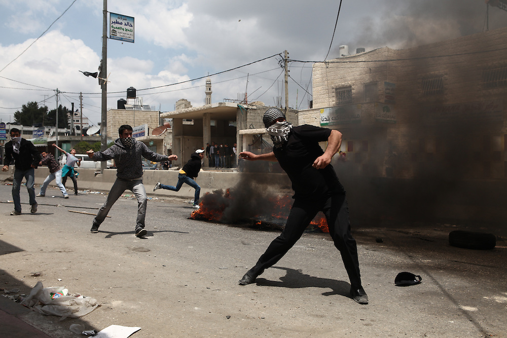 """A Palestinian protester throws a stone at Israeli security forces during clashes at Qalandiya checkpoint, near the West Bank city of Ramallah May 15, 2011. Israeli security forces had been on alert for violence on Sunday, the day Palestinians mourn the """"Nakba"""", or catastrophe, of Israel's founding in a 1948 war, when hundreds of thousands of their brethren fled or were forced to leave their homes"""
