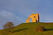 View of Burrow Mump, Somerset from the base of the hill, with the ruined church on the top. The church itself is lit by the new dawn.