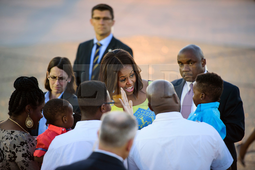 © Licensed to London News Pictures. 15/06/2015. Stansted, UK. First Lady MICHELLE OBAMA, pictured giving a high five to a young boy, speaking to the families of US servicemen who live in the UK as she arrives in the UK at Stansted Airport accompanied by her daughters Malia and Sasha for the start of a three day visit to the UK. During the visit the First Lady and her family will meet with students at Mulberrry School for Girls and have Tea with Prime Minister David Cameron and Samantha Cameron. Photo credit: Ben Cawthra/LNP