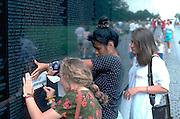 Visitors age 20 making rubbing at national Vietnam war memorial.  Washington DC USA