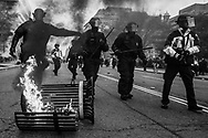 Police go after protestors during a demonstration after the inauguration of President Donald Trump, Friday, Jan. 20, 2017, in Washington. Protesters registered their rage against the new president Friday in a chaotic confrontation with police who used pepper spray and stun grenades in a melee just blocks from Donald Trump's inaugural parade route. Scores were arrested for trashing property and attacking officers.