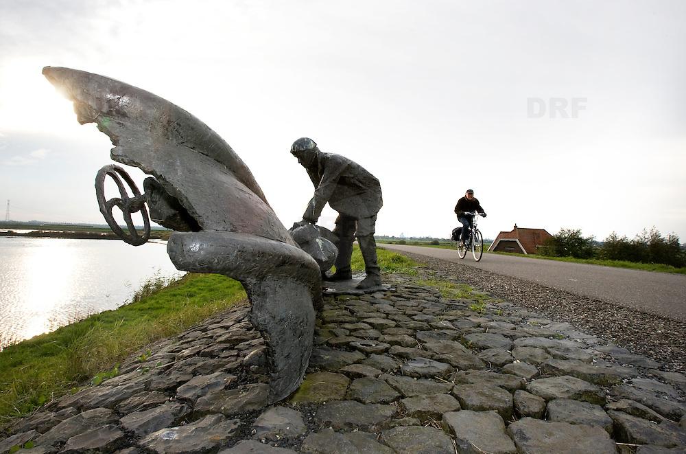 """Nederland Nieuwerkerk aan den Ijssel 2 november 2008 20081102 Foto: David Rozing ..Herdenkingsmonument """" Een dubbeltje op zijn kant """" op de Groenendijk.  Monument ter herdenking aan de watersnoodramp 1 februari 1953. Een dijkdoorbraak van Schielands Hoge Zeedijk bij Nieuwerkerk aan den IJssel werd tenauwernood voorkomen. Het water van de IJssel stond net onder de kruin van de Groenedijk. Nieuwerkerk en het achterliggende gebied werd gespaar omdat Schipper Evergroen op last van de burgemeester zijn schip in de dijk voer en zo het gat dichtte. Het monument beeld het schip en een persoon die zandzakken op het schip legt uit. Als de dijk was bezweken was het volgende gebied ondergelopen: tot Alphen aan den Rijn, Leiden,  Den Haag .  ..Tekst informatiebord bij monument: .""""Dubbeltje op zijn kant"""" herinnert aan de watersnoodramp van 1 februari 1953..Om 0.00 uur was het bij laagwater al NAP +2,60 m. Dit was meer dan de hoogste hoogwaterstand toen bekend. De noordwesterstorm nam toe tot orkaansterkte. De aanhoudende regen, hagel en natte sneeuw verzwakten de dijk. Met man en macht werden zandzakken aangedragen. Behalve de dijkbewaking werkten zo'n 100 mariniers mee. Bij NAP +3,00 m startten de voorbereidingen voor de evacuatie. Zo'n 3 miljoen mensen in het achterland werden bedreigd.?Om 4.00 uur werd NAP +3,84 m bereikt en spoelde er water over de onverharde dijk. Het water sloeg de binnenzijde stuk. Op sommige plaatsen was de dijk nog maar 1 meter breed!?Om 5.30 uur sloeg er een gat van 15 meter in de dijk! Er moest iets gebeuren. Burgemeester J.C. Vogelaar van Nieuwerkerk aan den IJssel vorderde het schip de Twee Gebroeders van A. Evegroen, dat in de buurt lag. De schipper zette de 'kop' van zijn schip in de dijk en zwenkte de achtersteven naar het gat. Als een sluisdeur sloot de Twee Gebroeders het gat. Daarna werd het met zandzakken gevuld. Toen de dijk bij Ouderkerk aan den IJssel doorbrak zakte de waterstand en nam de waterdruk af.?.Het monument is van het Hoogheemraad"""