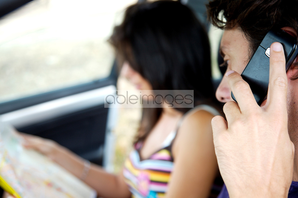 Close up of young couple inside a car looking at map man on the telephone