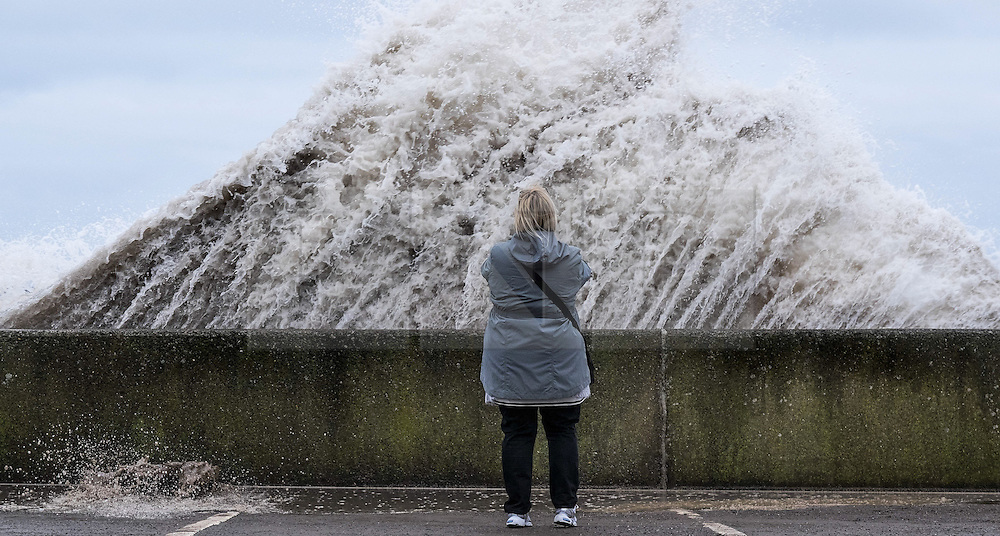 © Licensed to London News Pictures. <br /> 21/03/2015. <br /> <br /> Sandsend, North Yorkshire.<br /> <br /> A woman looks on as a huge wave crashes against the sea wall at Sandsend in North Yorkshire. The exceptionally high Spring tides were created by the moon's 18-year cycle.<br /> <br /> Photo credit : Ian Forsyth/LNP