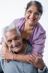 Portrait of an older woman with her arms around her husband's shoulders,
