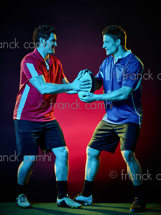 two caucasian rugby men players on colorful black background
