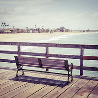 Seal Beach California pier bench retro tone photo with the Pacific Ocean and oceanfront homes. Seal Beach is in Orange County Southern California in the United States of America.