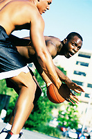 Two African-American men faceoff in a one-on-one game of basketball.