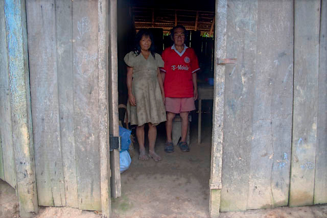 """A couple of awajun natives, members of a aguaruna community posses for a portrait at his house near to Imaza river-port of the Mara-on river in Amazons district, Peru. After the events of June 5 in the Amazonian province of Bagua, in northeastern Peru, where 24 policemen and a number still not confirmed of natives from the communities of the ÒAlto Mara-onÓ and civilians died in clashes after a series of demonstrations in opposition to the approval by the Peruvian government, for a group of ordinances that allow large flexibility in the restrictions on resource extraction in the area, breaking the 169 agreement of ILO (International Labour Organization), which requires the consultation of indigenous communities about the exploitation of nature in their territories. One of the most active communities was the awajun, a warlike and revengeful people, heritors of the Jibaros and recently contacted near to 1950. For the leader or """"apu"""" for one of the aguarunas riverside communities of the Mara-on, Simon Weepiu, Òthe force of this movement come from the conviction of the struggle, which is caused by the ancestral development as based on worldview, which provides the native of a special power, that of becoming one with his idea and his brothers, to focus all on the same objective and be just a great strength."""" The government aims to generate development in the area allowing the exploitation of property, The jungle is rich in gold and oil, and even argue that natural wealth of the region belong to all Peruvians, and not just the communities that inhabit it, but acts as the oil«s filtration to waters of the Mara-on, left in evidence that in a complex ecosystem like jungle that mixed spilled oil by rain in the river, home to fishes, as well as the waters that irrigate cassava, bananas, sugarcane and other elements vital to the development of communities. The natives, insist that the forest is not only home, is where they get medicines to cure their sick and food for their fami"""