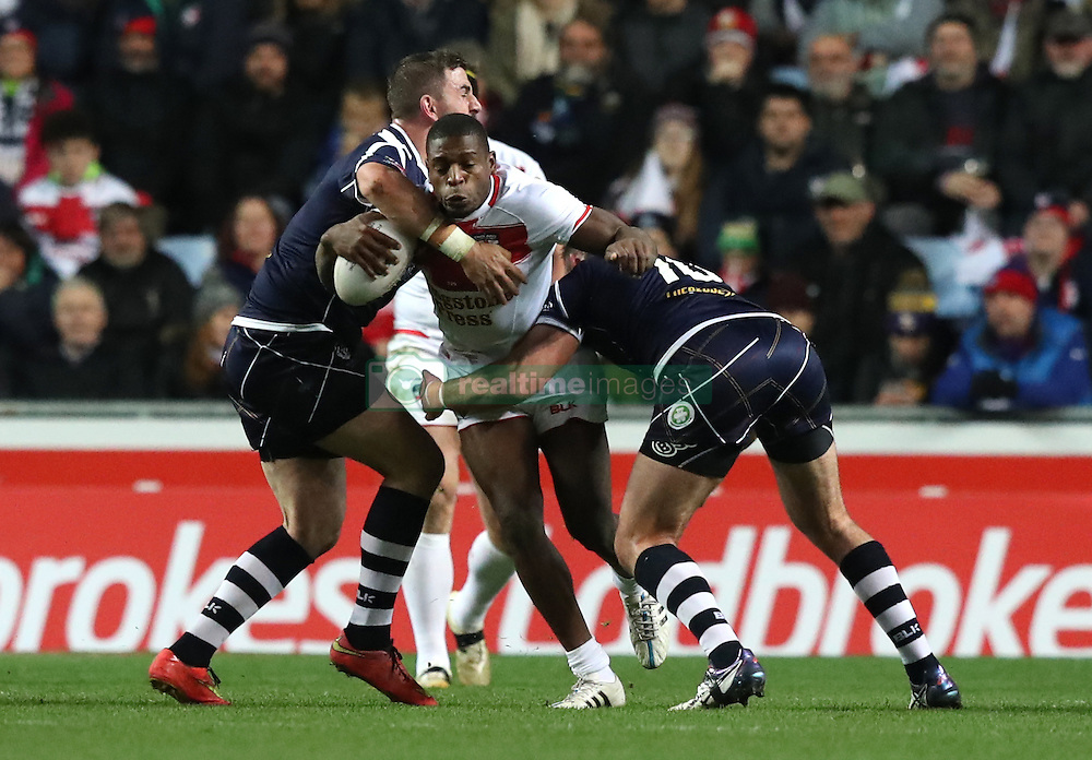England's Jermaine McGillvary (centre) is brought down by the Scotland defence during the Four Nations match at the Ricoh Arena, Coventry.