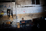 GAZA CITY, GAZA STRIP - JULY 8: Raed Ahmed Moussa, 14, sits in the workshop where he has been working since he was 13 on July 8, 2010, in Gaza City, Gaza Strip. With Gaza's economy devastated by years of sanctions and decades of conflict, many families send their children to work. Although Israel eased its blockade in mid-June - allowing in consumer goods - little has changed for Gaza's poorer families. Unemployment runs at 40% and the majority of the population is dependent upon aid handouts for their basic needs. (Photo by Warrick Page)