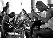 Men finishing wooden stools in a workshop, Ghana, Africa