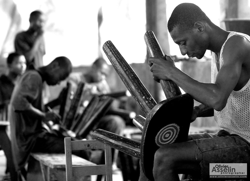 Men finishing wooden stools in a workshop, Ghana, Africa