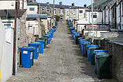 Wheelie bins lined up in a cobbled back street of terraced houses in Skipton, North Yorkshire, UK.