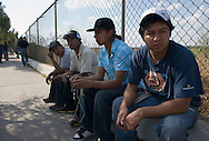 NEWS&GUIDE PHOTO / PRICE CHAMBERS.Exhausted from a multi-day drive, Cesar and the others relax in Nuevo-Laredo, Mexico as their vehicles' papers are approved by the government. Behind them is the mexican border and the Rio Grande river.