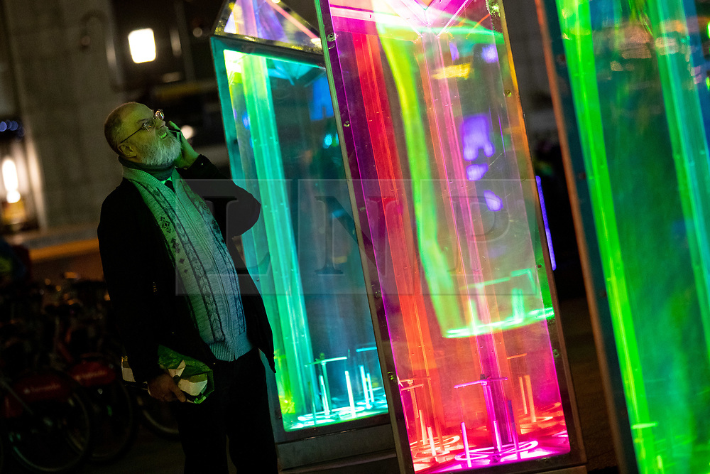 © Licensed to London News Pictures. 14/01/2019. London, UK. A member of the public looks at 'Prismatica' a light installation created by Raw Design as part of Canary Wharf's Winter Lights 2019. Photo credit : Tom Nicholson/LNP