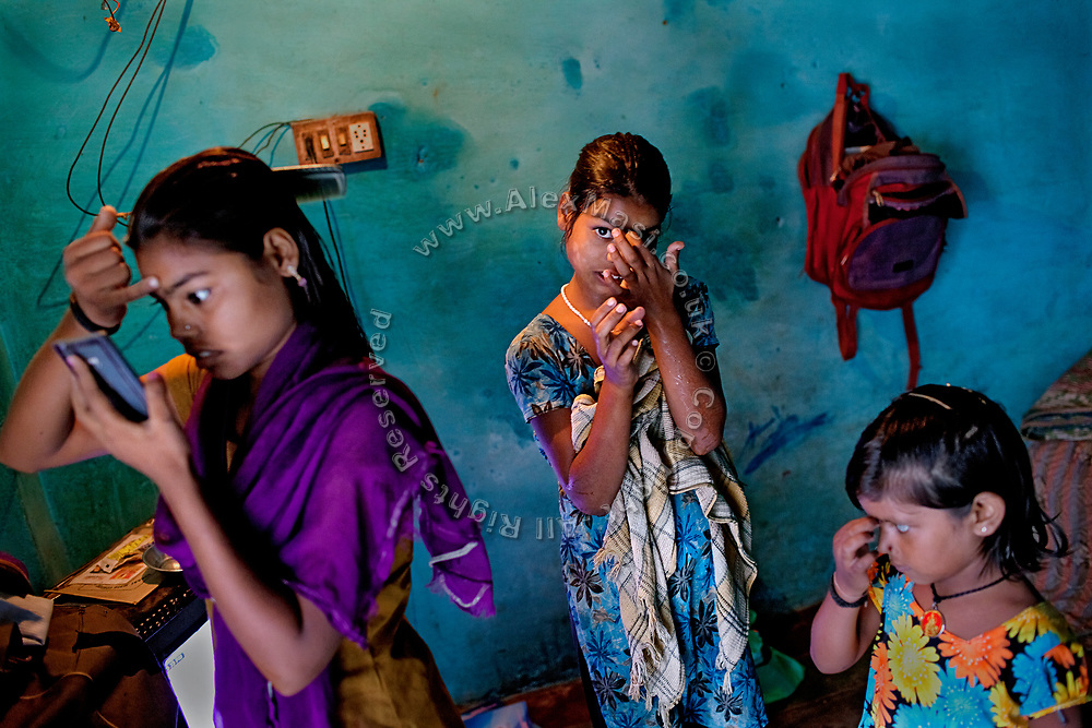 Poonam, 11, (centre) her older sister Arti, 17, (left) and their young friend Dipshika, 4, (right) are applying a Bindi decoration to their forehead while inside the family's newly built home in Oriya Basti, one of the water-contaminated colonies in Bhopal, central India, near the abandoned Union Carbide (now DOW Chemical) industrial complex, site of the infamous '1984 Gas Disaster'. A Bindi is a forehead decoration worn in South Asia. Traditionally it is a bright dot of red colour applied in the centre of the forehead close to the eyebrows.